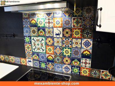 <p>bunt gemischtes Patchwork aus Mexambiente-Fliesen aus Mexiko in Kombination mit schwarzen grossflächigen Fliesen. Bunter Fliesenspiegel – Ikea Küche</p>