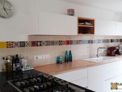 <p>Weiße Küche mit bunten mexikanischen Fliesen als Fliesenspiegel für die Rückwand</p> <p>Eine bezaubernd bunte Bordüre aus Premium handbemalten Dekorfliesen von Mexambiente (11×11 cm) Passend dazu: einfarbige Premium Fliesen in Perlweiß</p>